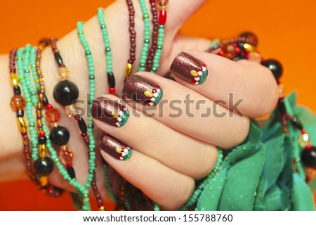 Women's nails are covered with brown varnish with the design of white,red and turquoise points on an orange background with a bracelet made of beads in the tone of the nail. - stock photo