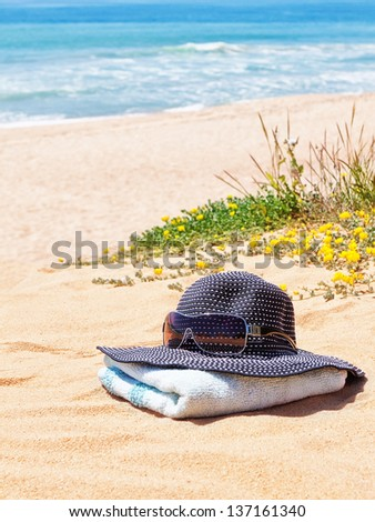 Women's Panama hat with sunglasses on a towel on the beach in the summer.