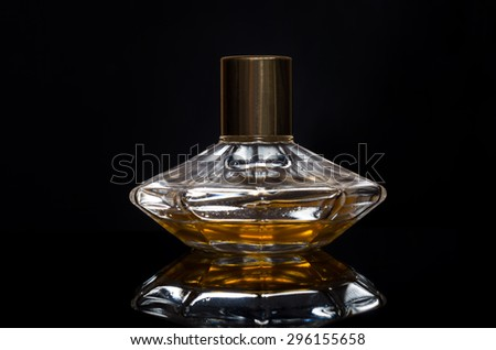 women's perfume bottle on a black background - stock photo