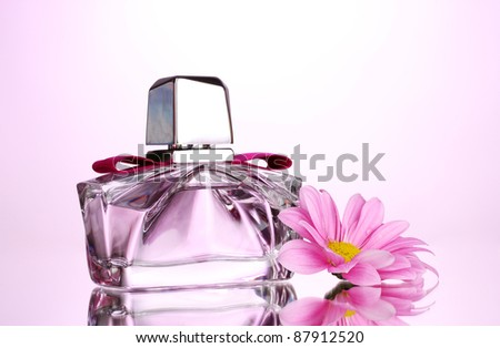 women's perfume in beautiful bottle and flower on pink background