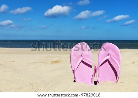 Women's pink flip flops alone on sandy beach - stock photo