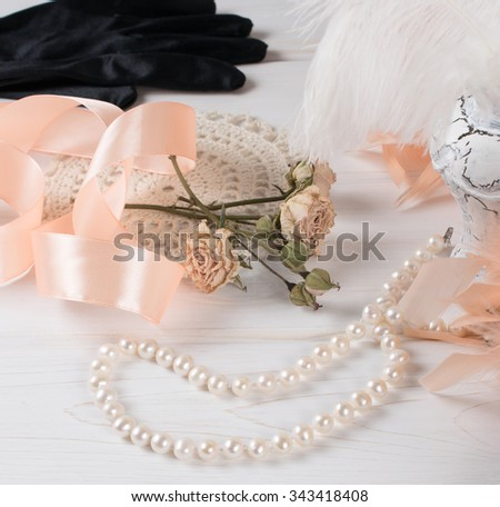 Women's retro accessories including velvet gloves and pearl necklace on wooden  table  - stock photo