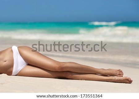 Women's sexy legs on the beach  - stock photo