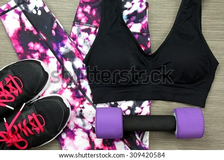 Women's sport wear and Dumbbell. Fitness wear and equipment. Sport fashion, Sport accessories, Sport equipment. - stock photo