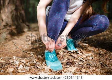 Women's sports sneakers on a background of forest trails in summer