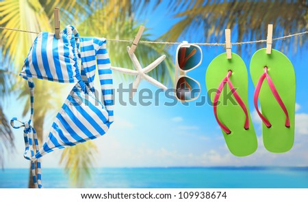 Women's swimsuit, sunglasses and flip-flops hanging on a rope near beach. - stock photo