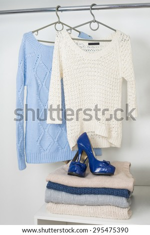 Women's warm knitted things in the white cupboard, two sweaters hanging on hangers, a pile of warm woolen clothes and lacquered blue shoes - stock photo