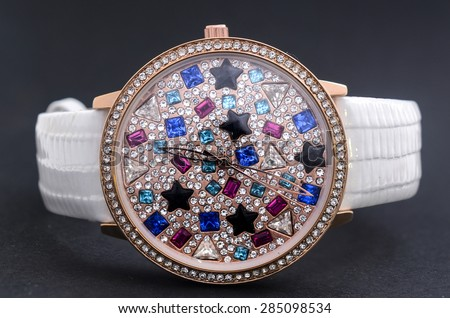 women's watches with gems on a black background - stock photo