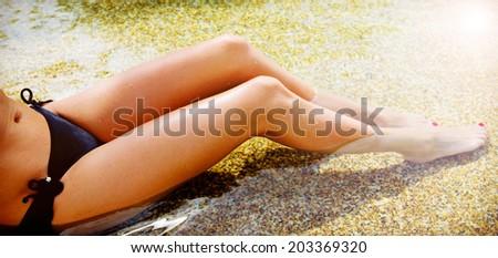 Women's wet  beautiful legs in  the water - stock photo