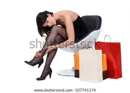 Women sat surrounded by shopping bags - stock photo