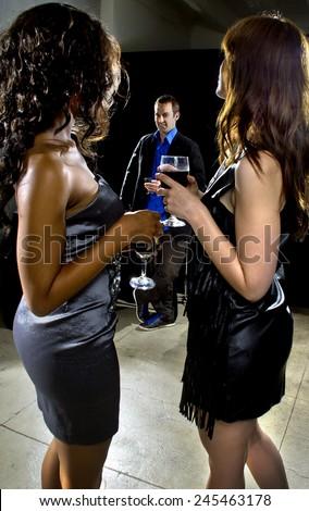 women seducing a man at a bar or nightclub - stock photo