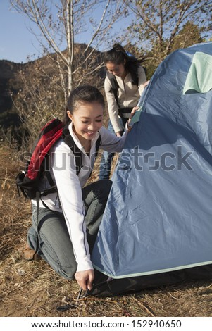 Women setting up the tent - stock photo