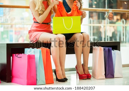 Women shopping. Cropped image of two young women sitting in shopping mall with bags