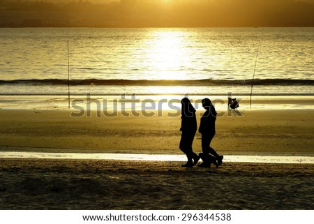 women silhouettes walking in the beach at dusk  - stock photo