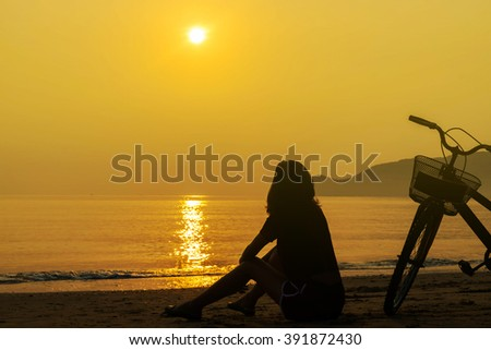 Women site on the beach seaside during sunrise and orange sky. silhouette concept - stock photo