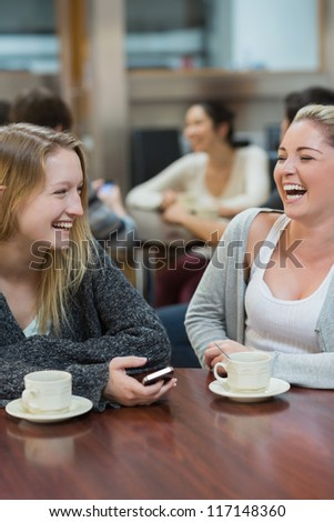 Women sitting at the college coffee shop drinking coffee while laughing - stock photo