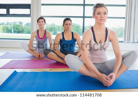 Women sitting in bound angle yoga pose in fitness studio - stock photo