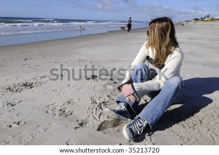 Women sitting on beach, in winter clothing, Mount Maunganui, New Zealand