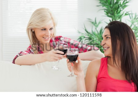 Women sitting on the couch drinking wine together at home - stock photo
