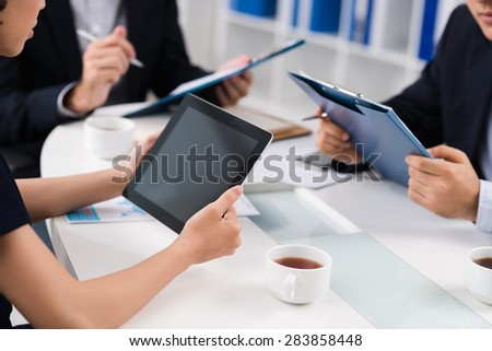 Women sitting with touchpad at important meeting - stock photo