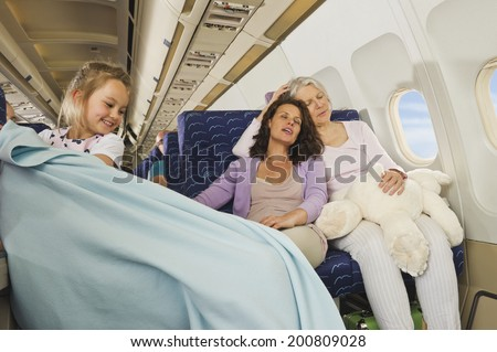 Women sleeping and girl pulling blanket on airplane - stock photo