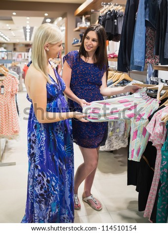 Women  standing at a clothes rail and smiling at a shopping mall - stock photo