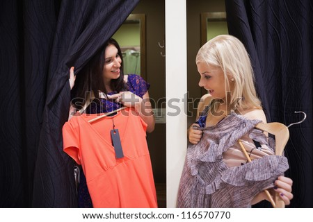 Women standing in a changing room of a boutique talking - stock photo
