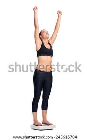 Women standing on scale cheering for achieving her weight loss goal isolated on white background - stock photo