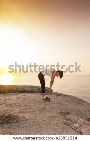 women stretching after sport  with the sea is background and sunrise in morning - stock photo