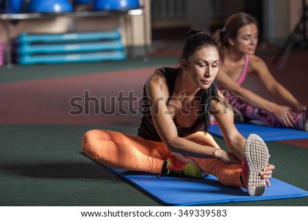 Women stretching legs on the floor in the gym