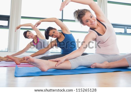 Women stretching on the floor at yoga class