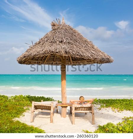 Women sunbathing on dack chair under wooden umbrella on stunning tropical beach. Turquoise blue lagoon of Paje beach, Zanzibar, Tanzania in the background. - stock photo