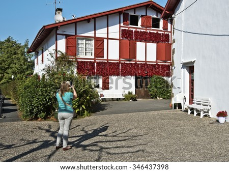 Women take photo with her Smartphone of traditional Basque house with Red Peppers drying on the wall, Espelette village in traditional Basque province of Labourd, France, Atlantic Pyrenees, Aquitaine  - stock photo