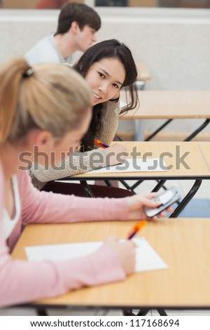 Women talking and texting during class in college - stock photo