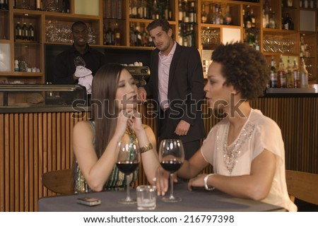 Women talking, man looking at them in the background.