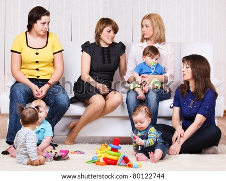 Women talking, their children playing - stock photo