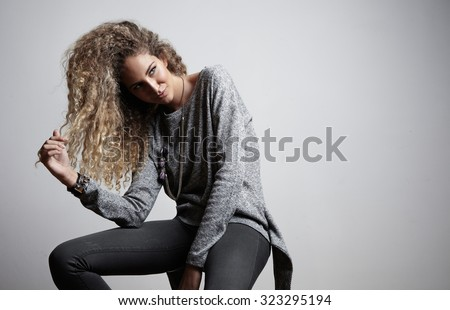 women touching her blond curly hair - stock photo