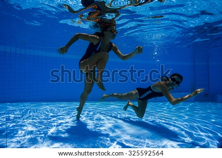 Women under water runs along the bottom of a swimming pool - stock photo