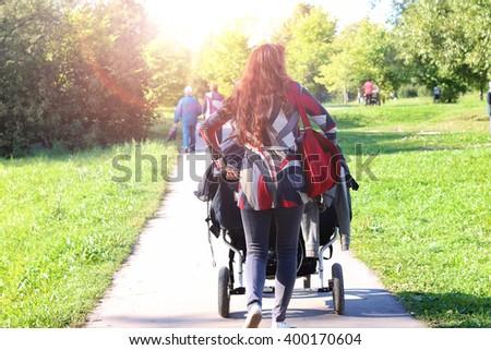 women walk stroller summer sunlight - stock photo