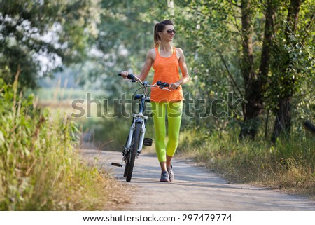 Women walking with bicycle in the forest - stock photo