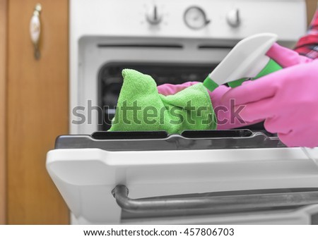 Women washed gloved hands inside oven. Close-up.