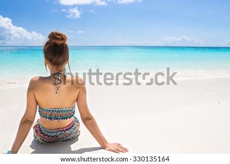 women wear bikini sitting on the beach - stock photo