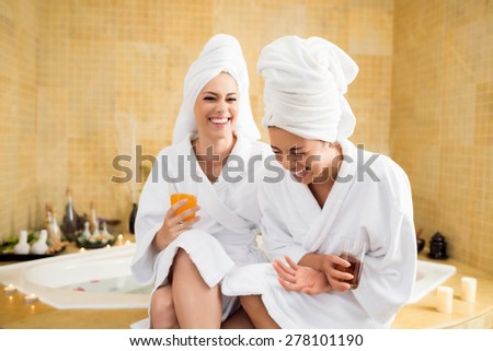 Women wearing bathrobes laughing together in spa center - stock photo