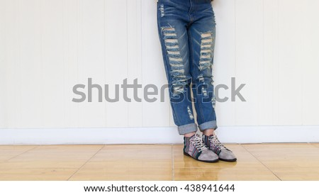Women wearing jeans and Striped shoes Standing against a white wall