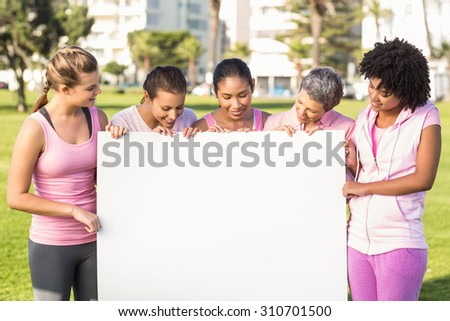 Women wearing pink for breast cancer and holding blank poster in parkland - stock photo