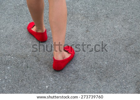 Women wearing red shoes walking on the street in the city - stock photo