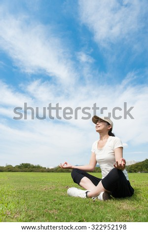 Women who have a pose of yoga on the lawn