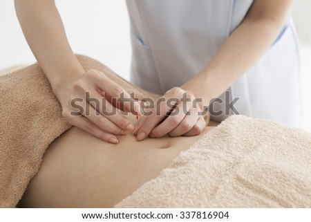 Women who have an acupuncture treatment in stomach for diet - stock photo