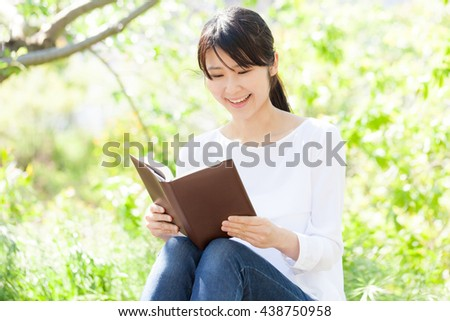 Women who read a book , outdoor , smile