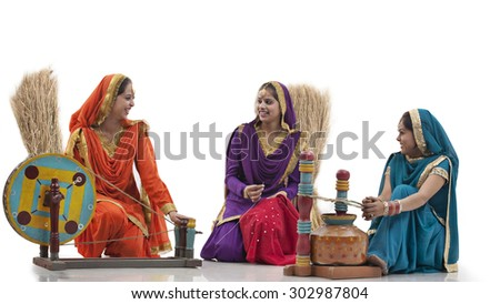 Women with a spinning wheel and a butter churner